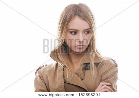 Beauty in coat. Portrait of attractive young woman in coat looking away while standing against white background