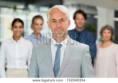 Successful mature businessman standing with businesspeople behind. Portrait of senior manager looking at camera in front of his business team. Happy smiling executive in suit.
