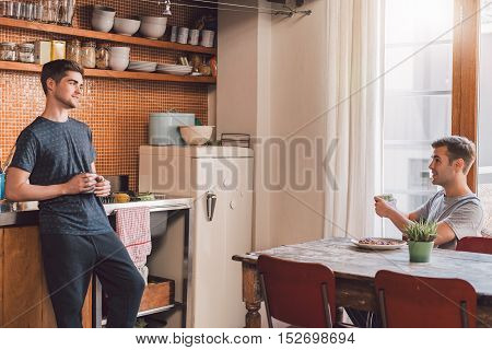 Smiling young gay couple drinking coffee and talking together in their kitchen in the morning