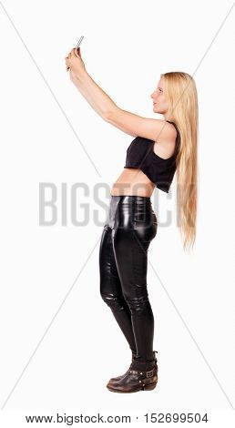 back view of standing young beautiful  girl with tablet computer in the hands of. girl  watching.  Isolated over white background. Blonde in leather pants photographing something in the sky.