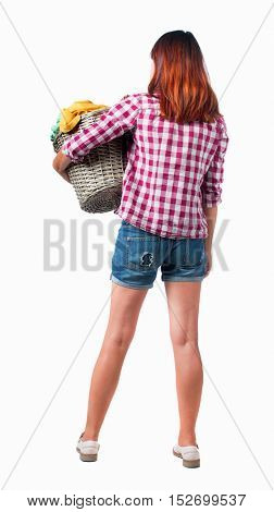 Back view of woman with  basket of dirty laundry. girl is engaged in washing. Rear view people collection.  Isolated over white background. Girl in shorts and shirt holding a basket of laundry.
