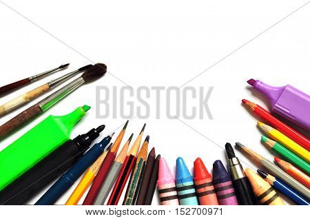 A set of color tools for drawing on a white background close up: markers crayons paints pencils. Space for text.