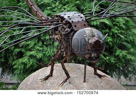 Grodno, Belarus - July 15, 2016: Street art in Grodno, Belarus. Dragonfly of rusty metal in the steam-punk style sits on a natural stone.
