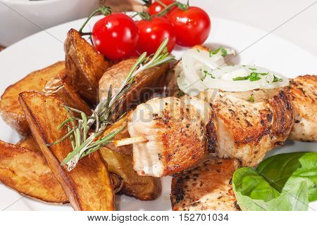 kebab with baked potatoes cherry tomatoes basil and rosemary