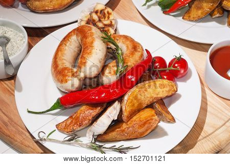 grilled sausages with baked potatoes cherry tomatoes Red pepper basil and rosemary