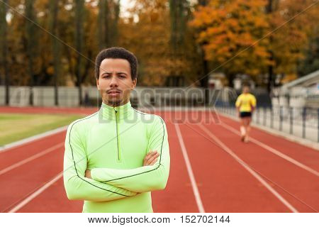 Sprinter stands in the stadium. The dark-skinned man in training