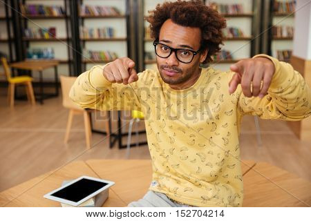 Handsome african american young man in glasses pointing on you with both hands in library
