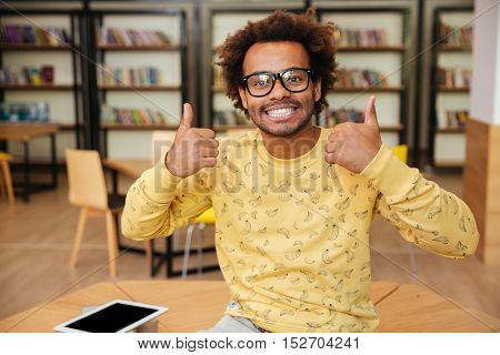Cheerful african american young man in glasses showing thumbs up with both hands in library