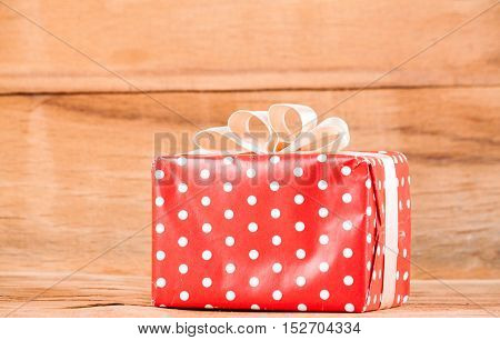 Red gift box on wood desk. Christmas concept
