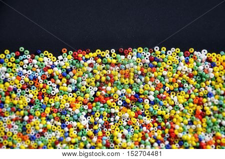 Multicolor beads on a dark surface with space for text at the top. Background texture.