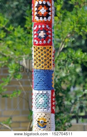 A street pole tied with colored woolen threads with a pattern. Close up. Selective focus.