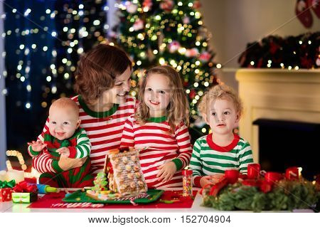Mother And Kids Making Ginger Bread House On Christmas
