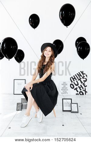 Smiling pretty young woman sitting over background with white boards and balloons