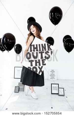 Happy beautiful young woman holding poster and laughing over white background