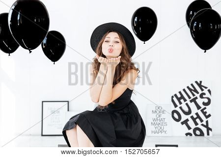 Happy pretty girl sending a kiss over white background with black balloons and posters