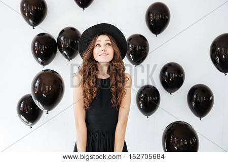 Pretty inspired young woman standing and looking up over white background with black air balloons