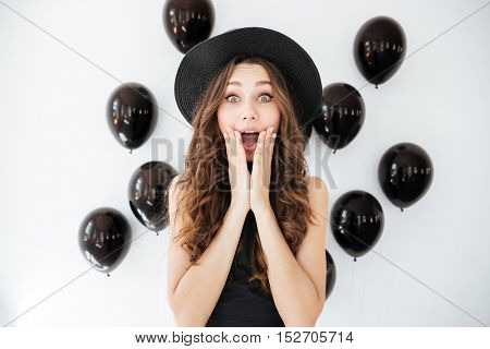 Happy surprised young woman with opened mouth over white background with black air balloons