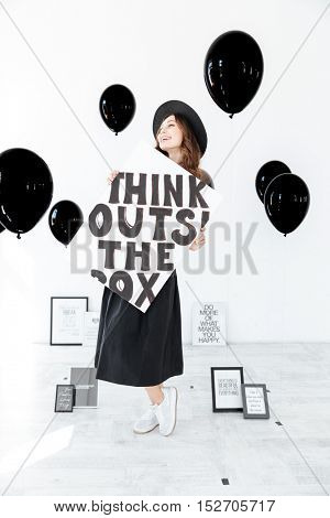 Smiling attractive young woman with black balloons standing and holding poster over white background