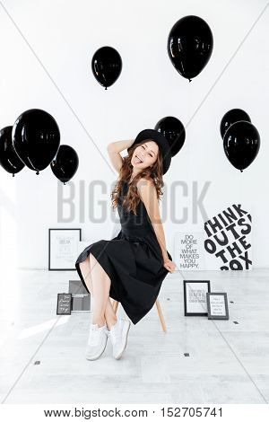 Playful young woman with posters and black balloons sitting and showing tongue over white background