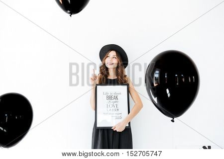 Happy pensive young woman holding poster and pointing up over white background