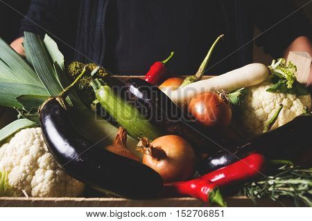 Farmer holding in his hands wooden box with local organic vegitables. Local organic food concept