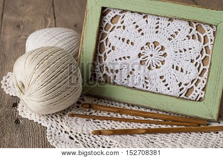 Openwork knitted napkin in a wooden frame, tangles of threads and crochet hooks on an old wooden table.