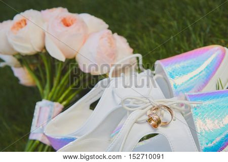 wedding bouquet and shoes lying down on green grass. Retro style