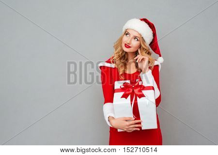 Smiling wondered woman in red santa claus outfit holding christmas gift isolated on the gray background
