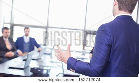 Business man making a presentation in office. Business executive delivering a presentation to his colleagues during meeting or in-house business training, explaining business plans to his employees.