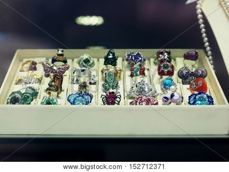 Window display at jewelry shop presenting   rings and earring sets.