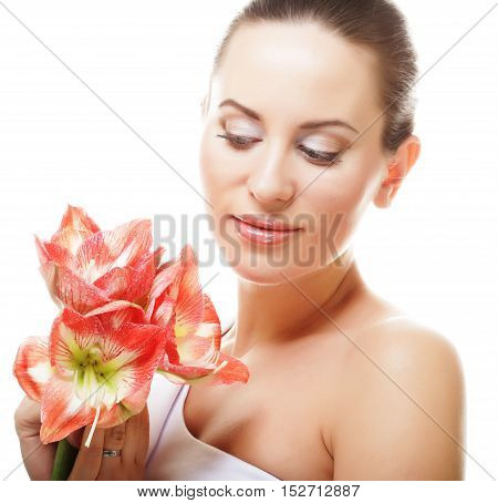 People, health and spa concept: beautiful young woman with big pink flowers
