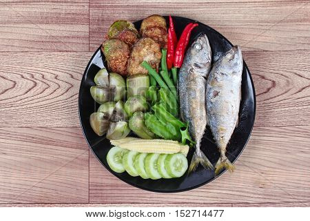 Ready side dish served  for Thai spicy sour dip   as deep fired mackarels,boiled long-eggplant,lentils,winged bean ,red hot chili pepper and sliced cucumber on wood.  Have text space for fillin.