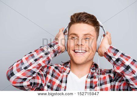 Portrait Of Happy Young Man  Listening Music In Headphones