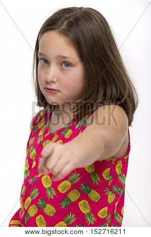 A young girl pointing at someone as to accuse.