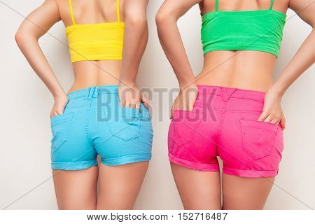 Close up photo of sexy woman's backs in color shorts hands in pockets