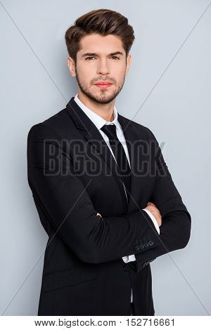 Portrait Of Serious Young Businessman In Black Suit With Crosed Hands