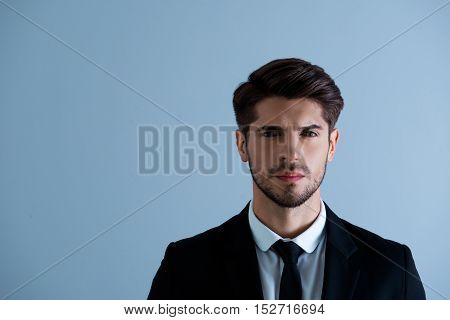 Portrait Of Serious Brutal Young Man In Black Suit