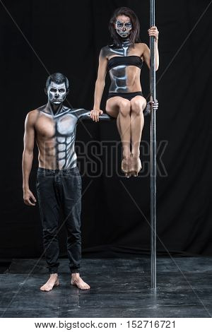 Serious couple of pole dancers in the dark studio. Man holds a pylon with the left hand. Girl sits on the guy's left arm. They wear black sportswear and have a horrific body-art. Vertical.