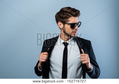 Portrait Of Handsome Macho Man In Glasses Touching His Suit