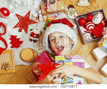 little cute kid in santas red hat with handmade gifts, toys vintage wooden, warm winter, lifestyle people concept close up