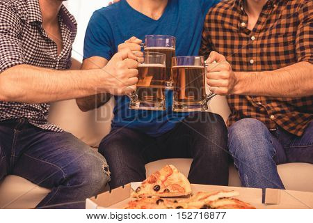 Close Up Of Three Football Fans Clinking With Glasses Of Beer