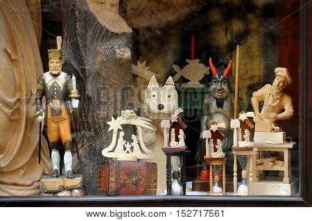 Cesky Krumlov, Czech Republic - April 14, 2016: Czech Showcase store with wooden sculptures. Vintage carved human figures a wolf and a devil closeup.