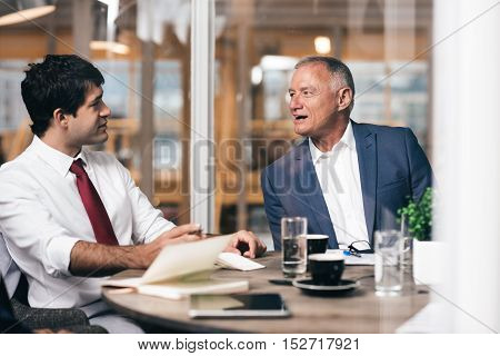 Mature businessman talking with a young staff member while sitting together at a table in an office boardroom