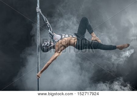 Handsome pole dancer with horrific body-art hangs horizontal on a pylon in the dark studio on the background of a cloud of a smoke. He holds the pylon with the hands and looks up. Horizontal.