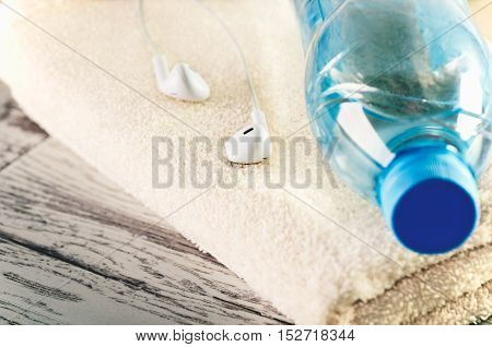 tinted image white headphones and a bottle of water close-up on a terry towel horizontal