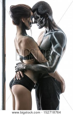 Sweet couple of pole dancers with horrific body-art stand in the studio on the white background. They are hugging each other. Guy and the girl dressed in black sportswear. Vertical.