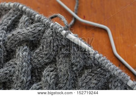 The process of knitting a hat with extensive cabling.
