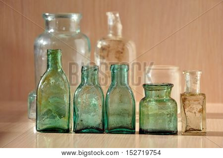 Small different green glass vintage bottle closeup.