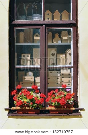 A window with various carved wooden birdhouse and boxes standing inside. Pots with red geranium flowers standing on the windowsill.