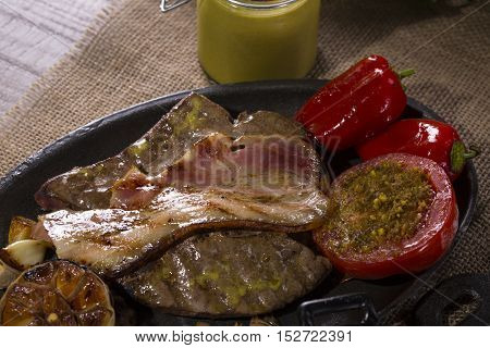Still Life food dish of veal liver with bacon and tomato baked with pistachios, roasted garlic, mustard and a pot of mashed potatoes